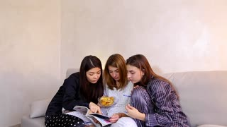 Three wonderful women together hold fashionable women's magazine in their hands and read articles or view bright pictures, eat potato chips, chat and gossip, sitting on gray sofa in bright bedroom at