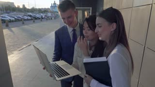 Three Young Students, Girls and Boy Work With Laptop and Talking on Background of Business Center Outdoors in Neutral Colors.