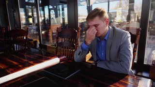 Tired young professor sitting at cafe with roll paper, smartphone and tablet on table