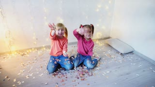 Two kids waving hands at home christmas party