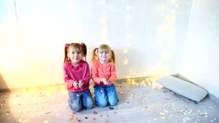 Two little girls sit on floor at Christmas studio