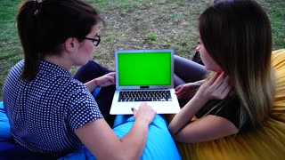 Two Lovely Girlfriends Look at Advertising on Internet on Green Screen and Discuss Sitting in Soft Armchairs Outdoors in Park on Warm Day.