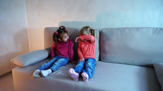 Two sisters sitting on couch, little girl cries
