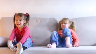 Two sisters sitting on couch, older child playing, little girl offended and angry