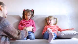 Two small girls sitting on couch, mom makes comment for bad behavior