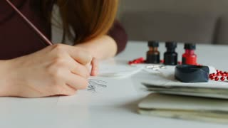 Unemployed woman indites resume for position of calligrapher at workshop