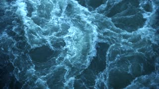 Water bubbles and creating big, strong waves. Aqua dark blue colored and has white foam. Concept of water storm big waves ocean