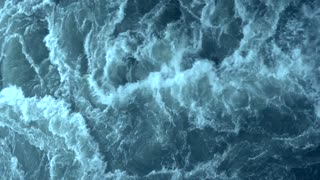Water creates strong waves. Aqua dark blue colored and has white foam. Concept of water storm big waves ocean wild places