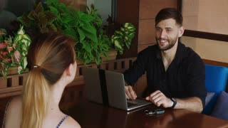Woman hiring flat and speaking with broker giving keys near laptop in slow motion