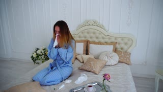 Women Caught Cold and Treated With Medication and Sitting on Large Bed in Bedroom.