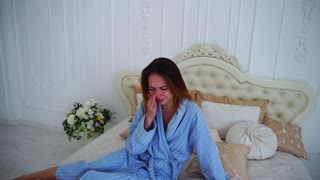 Women in Bad Mood, Upset and Crying, Sitting on Bed in Spacious Bedrooms.