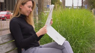 Young female person reading newspaper in park, sitting on bench near road in slow motion. Concept of resting with mass media outside. Pretty woman dressed in black turtleneck sweater has blonde hair.