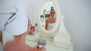 Young Girl Admires Himself and Looks Into Reflection in Mirror, Smiling and Open Jar of Cream, Sitting on Chair at Table in Bright Bedroom.