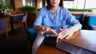 Young girl entering pin code on magnetic card reader at restaurant