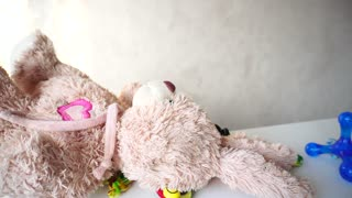 Young girl takes favorite toys from cupboard