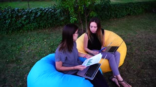 Young Girls Auditors Check Activities of Organization Working at Computers in Outdoor Park in Afternoon Sitting in Soft Armchairs.