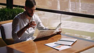 Young handsome man drinking water, reading newspaper at table near laptop