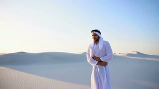 Young male emirate suffers from severe pains in abdomen, standing in middle of sandy desert on warm summer day