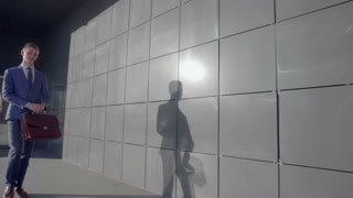 Young Male Manager Walk Along and Looks at Clock on Hand on Background of Business Center Outdoors in Neutral Colors.