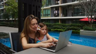 Young mother and female child enjoying with social network and using laptop with swimming pool background in slow motion. Concept of spending free time on summer resort and sending message to close