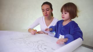 Young mother helps daughter with drawing, concentrated girls sitting in well-lit room discussing occupation