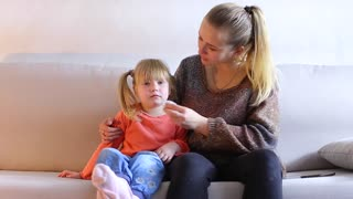 Young mother sits on sofa with daughter and wipes baby nose