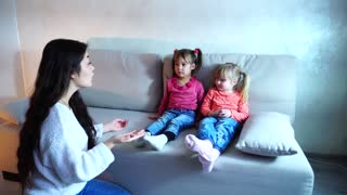 Young mother tells two daughters to gather in kindergarten