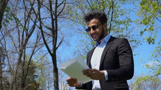 Young student reading diploma work and smile with dimples in slow motion