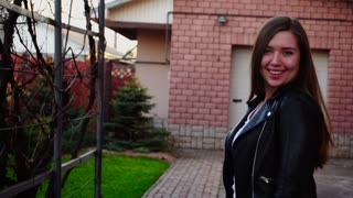 Young woman dressed in black leather jacket passing near garage, smiling and looking at camera. Concept of renting house and spring weather.