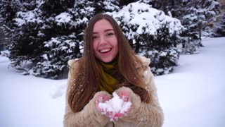Young woman play with snow