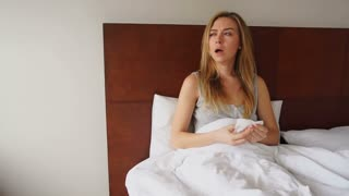 Young woman resting in bed with temperature and runny nose. Concept of flu symptoms and staying at home.