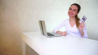 Young woman sitting near table with silver laptop and demonstrating money on camera