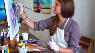Woman Sitting and Painting at Easel. Artist Mixes Paint on Palette With Brush and Paints on Canvas Picture, Sitting on Chair at Table in Art Class.