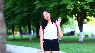 Woman waves hand and smiles to camera and touches hair on a gree
