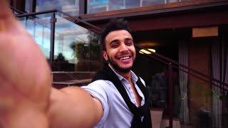 Young Arab Guy Takes Selfie With Camera Hand, Looking at Camera and Smiling on Background European Business Restaurant Stairs