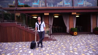 Young Arabian Male Man Entrepreneur Standing Waiting With Travel Bag in Hand, Smiling at Camera on Background of Restaurant With Hand in Pocket.