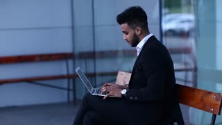 Young arabic business man uses laptop outside building background