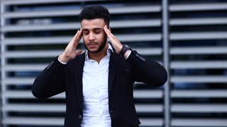Young Arabic Man Shows Neck Pain Tired in Business Center