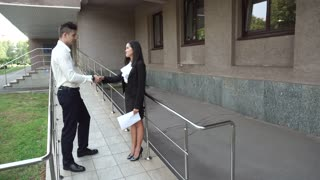 Young Beautiful Asian Business Woman Female and Caucasian Male Shake Hands Talk on Office Building Stairs