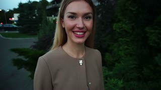 Young Beautiful Blond Woman Portrait Smiling Walking Around City in Evening