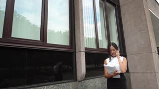 Young Beautiful Business Woman Female Girl Portrait Talk on Phone Hold Documents Stands on Background Office Building Outdoor