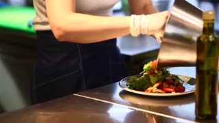 Young beautiful girl hands cook pours bowl ready-made meals in cafe restaurant