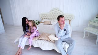 Young Family Quarrel, Husband of Wife and Daughter Sitting on White Bed in Room