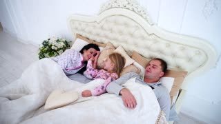 Young Family With Daughter Lie in White Room on Bed, Girl Woke up