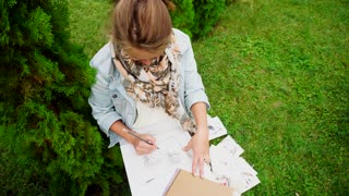 Young Girl Artist Draws Pencil on White Paper, Drawing and Holding Board With Sheets on Knees, Sitting in Park Outdoors in Daytime.