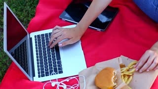 young lady hand woman presses the keyboard and eating fast food on the green grass