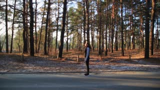 Athletic middle aged woman stretching in the green leaved woods on a dirt road before a run. Healthy life style concept