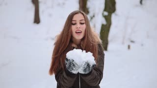 Christmas Girl. Winter woman Blowing Snow in the forest. Professionally colour corrected