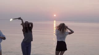 Close up shot of girls with sparklers celebrate, laugh and dance at the beach in sunset