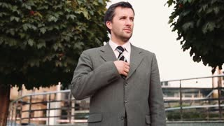 Confident businessman in suit using smartphone outdoors with office building and trees at background